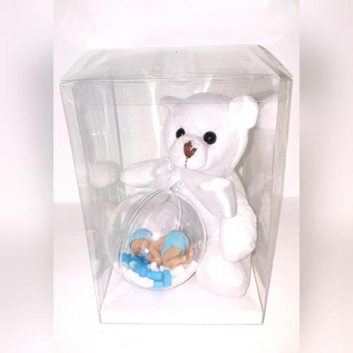סוכריית תינוק מתוק על מצע סוכריות בתוך בועת פלסטיק שקופה לצד דובון פרוותי לבן במארז מלבני שקוף מעוטר בסרט סאטן