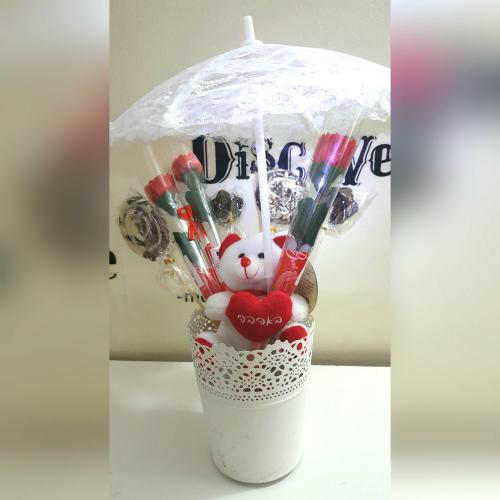 זר שוקולד דובון פרוותי מונח בכלי דקורטיבי יחד עם פרחים משוקולד ומטרית תחרה ארוז בצלופן עם סרט סאטן מהודר